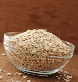 15565049-oatmeal-in-glass-bowl-shot-with-wooden-background